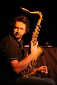 Julien Wilson holding his saxophone